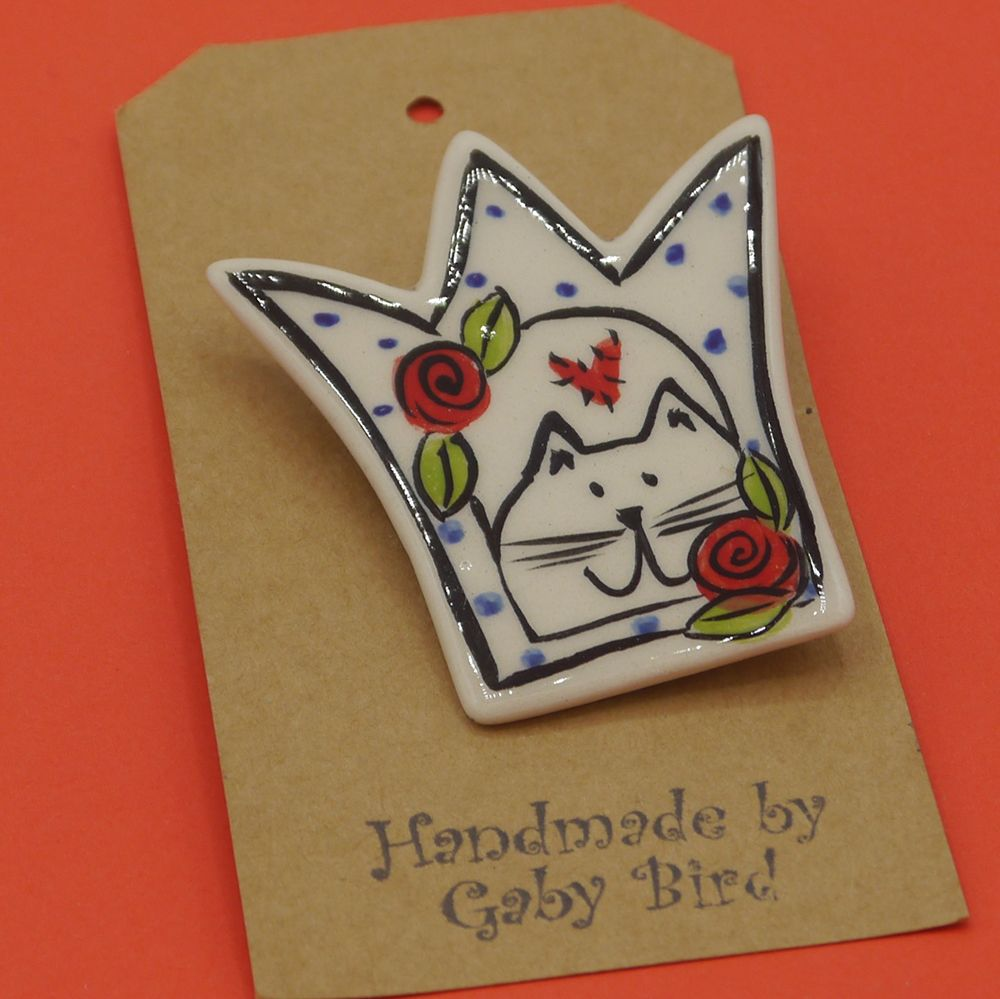 "Image Description of ""Gaby Bird – crown and cat brooch""."