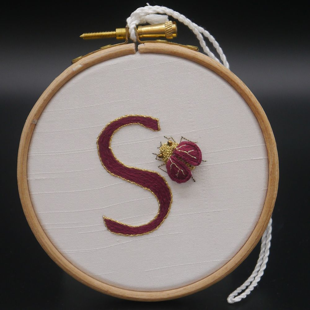 "Image Description of ""Ann Notley – hoop with monogram 'S' and embroidered beetle""."